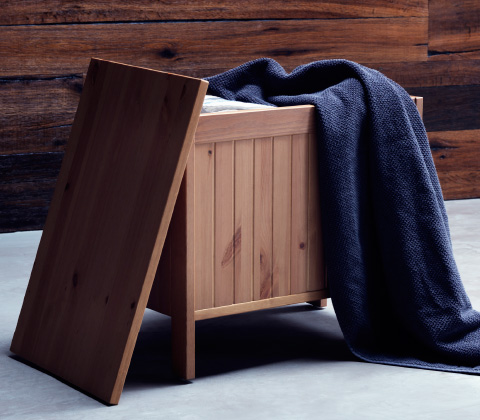 A close up image of a wooden storage bench open and filled with bathroom towels.
