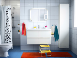 A bathroom with white tiles, white GODMORGON washbasin and cabinet and an orange rug