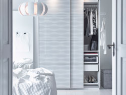 A bedroom with a white wardrobe with patterned sliding glass-doors