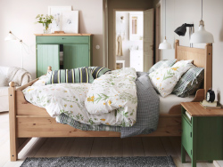 A green bedroom with HURDAL bed in solid wood, SISSELA flowery bed linen and green HURDAL storage