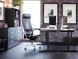 A modern office with two black-brown/white desks in front of each other with black swivel chairs