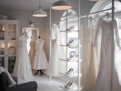 A wedding shop with white display shelves and glass-door cabinets