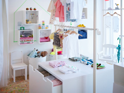 A boutique for children's clothes with white display shelves and storage benches