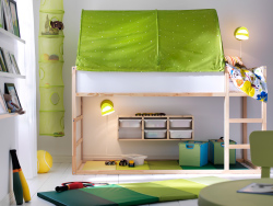 A small kids' bedroom with plenty of space for both sleep and play, with a KLURA loft bed in solid pine and a green KURA bed tent.
