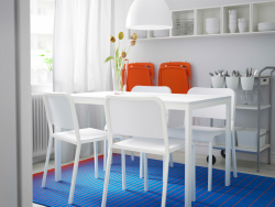 A small dining room with MELLTORP table and chairs in white, orange NISSE foldable chairs and blue MEJLBY rug