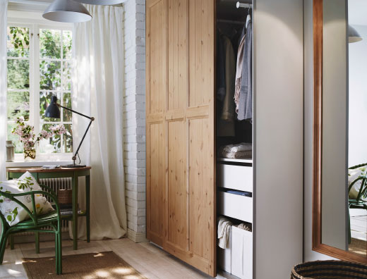 A small hallway with a PAX wardrobe with HURDAL sliding doors in solid pine, and a green ARKELSTORP table