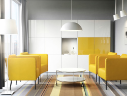 A modern conference room with yellow armchairs, a white round coffee table and white storage with some yellow doors