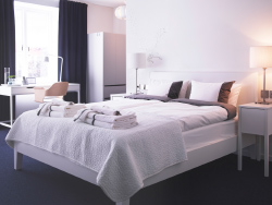 A hotel room with a white bed for two, bedside tables and a desk.