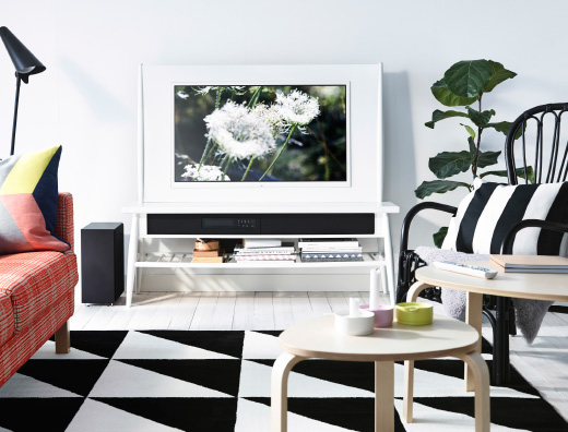 A white living room with an UPPLEVA HIMNA TV in white, an orange KARLSTAD sofa and an IKEA PS 2014 grid rug