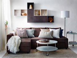 A modern living room with a brown FRIHETEN sofa bed, VALJE wall cabinets in brown and white and a white STRIND coffee table