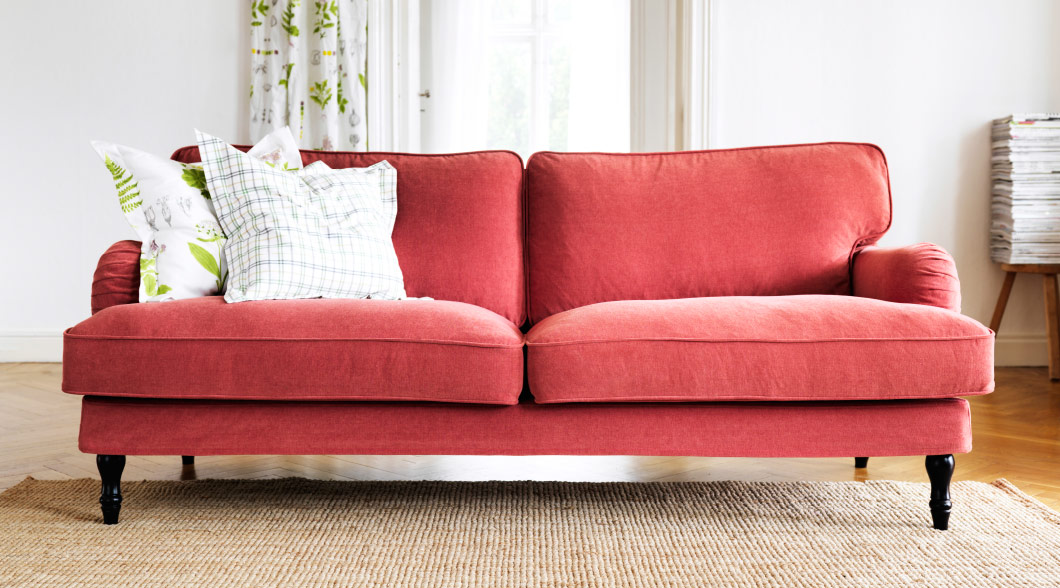 A large red sofa with colorful cushions in a white room.