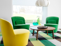 STOCKHOLM swivel easy chairs in Sandbacka yellow and green with STOCKHOLM round coffee table in walnut veneer