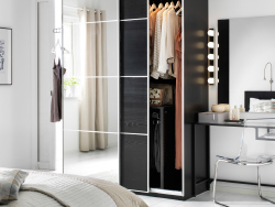 A white bedroom with a dark PAX wardrobe combination with a mix of dark wood and mirror glass sliding doors.