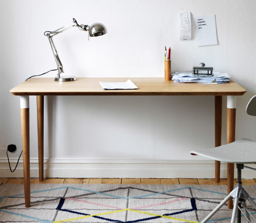 A wooden desk with a metal lamp on top against a white wall.