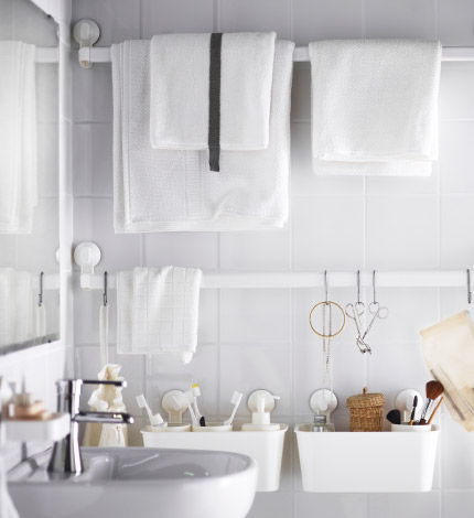 Two white towel hangers and four white basked attached with suction cups to a white tiled bathroom wall. On another wall a hook and a soap dish also mounted on with suction cups.