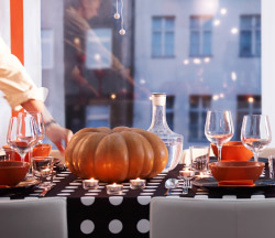 A dining room table decorade with black and organge decoration for Halloween