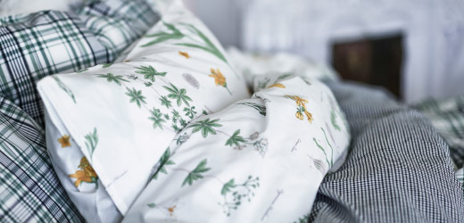 A bed made up with two kinds of bed linen. One has a flower pattern, the other a checked pattern.