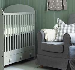 A nursery with Children's IKEA changing table, cot, armchair, rug and floor lamp.