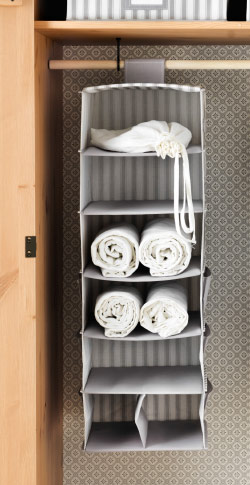 a grey clothes organiser in an open drawer showing clothes organised in different compartments.