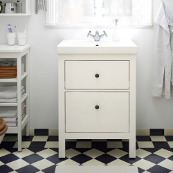 A white wash-stand on a chequered black and white tile floor.