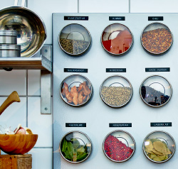 Kitchen with spice storage made of magnetic jars on magnetic boardsSEO Friendly Name: On a white tiled kitchen wall hangs a silver coloured magnetic board with stainless cointainers with clear lids on it