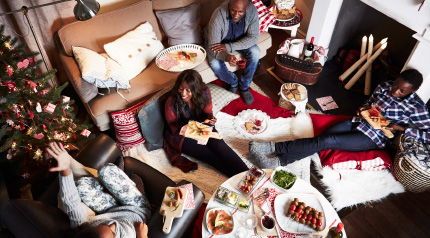 A family sitting in their living room eating Christmas dinner, picnic style. Two are sitting on the floor, one on the sofa and one on an arm chair.
