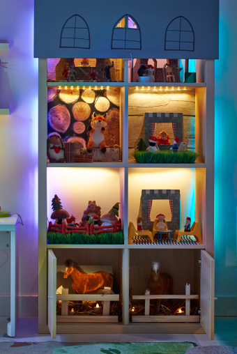 A bookshelf used as a toyhouse and filled with toys. LED strip lights light up each compartment and there is blind hanging over the front at the top with windows cut into it. There is a child's desk and lamp to the left.