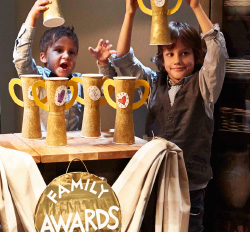 Two young boys and a girl hold up handmade trophies while standing behind a makeshift podium in the corner of a room.