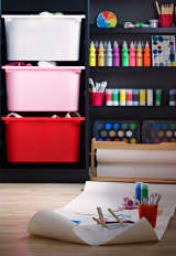 Bedroom with a blackboard wall and IKEA storage holding lots of colourful paints.