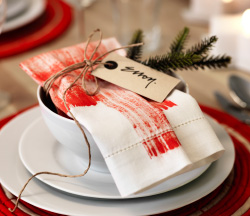 A close up image of a red painted napkin folded and wrapped with twine and foliage and placed over a bowl on a table setting.