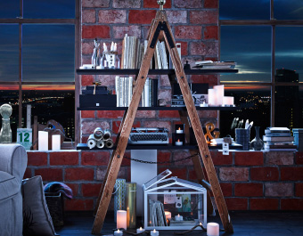 A step-ladder turned into a bookcase using shelves and filled with books and literature-themed trinkets infront of a brick wall with two large windows showing a city scene at night.