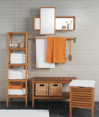 Light brown bathroom storage in a room with grey tiles.