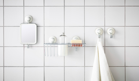 Bathroom accessories attached with suction cups to a white tiled wall.