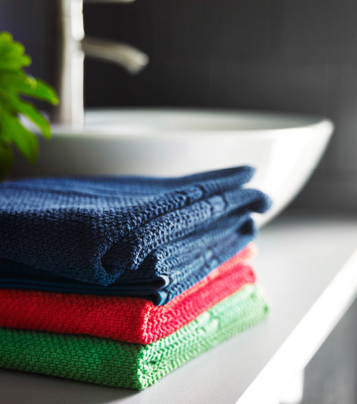 A pile of cotton hand towels in blue, red and green.