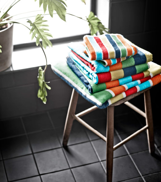 A pile of multicolored towels on a wooden stool.