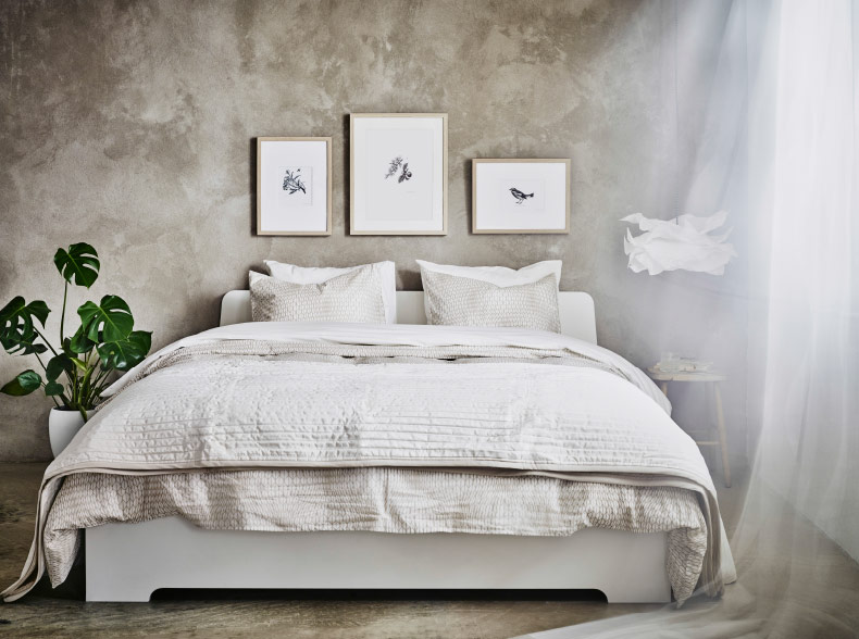 A white bed with bed textiles in beige and white.