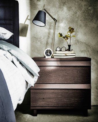 A chest of 2 drawers in stained ash veneer with a table lamp and alarm clock on top.