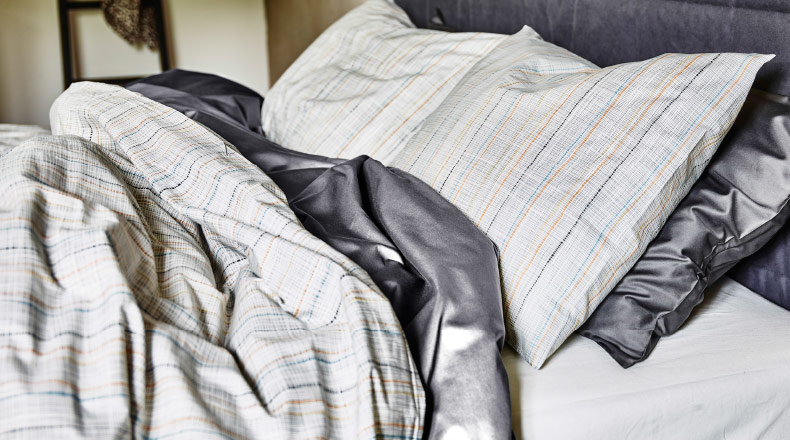 Close-up of a beige striped quilt cover and pillowcases.