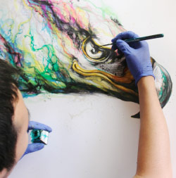 A street artist painting an eagle.