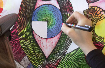 A street artist painting a colourful motif.