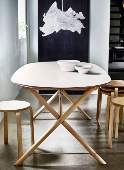an oval shaped dining table with white table top and birch legs shown