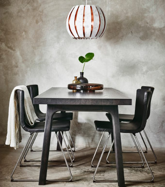 A black dining table and dark brown leather chairs with chrome-plated legs.