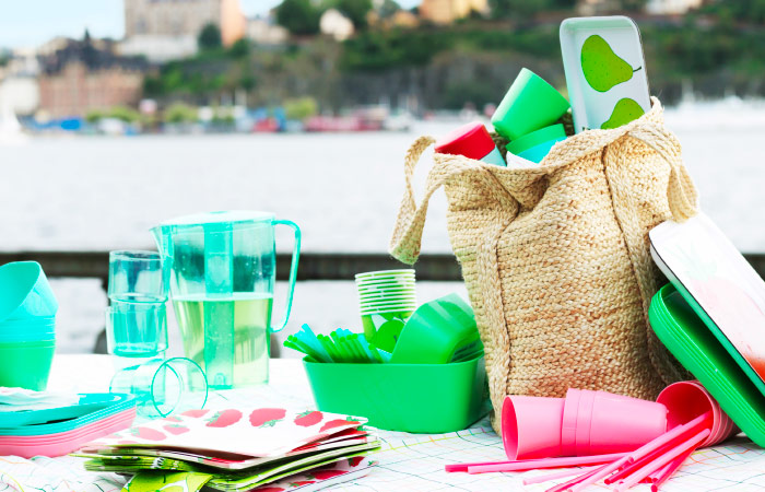 A blanket on the pier set with plastic glasses, plates, bowls, jug and drinking straws in bright colours.
