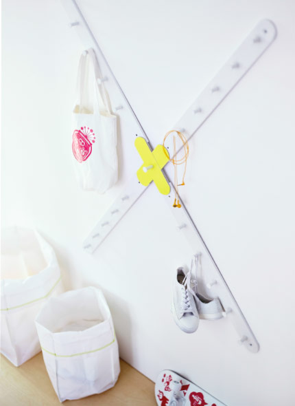 A white knob rack, shaped as a cross, hanging on the wall.