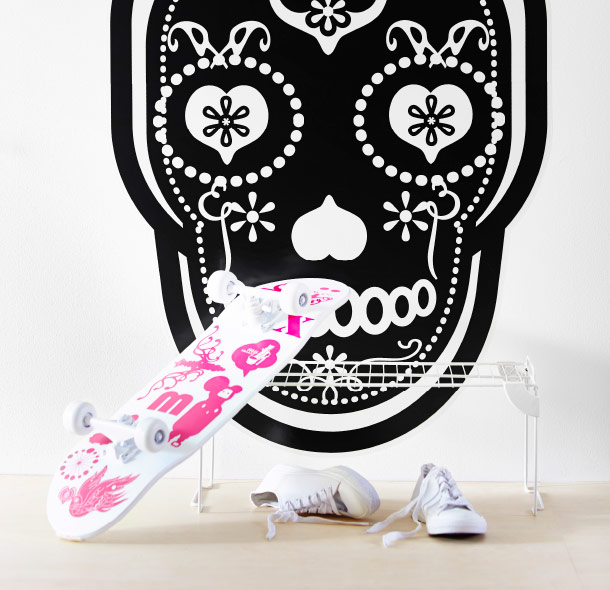 A black decoration sticker on a wall, shaped as a skull, and pink decoration stickers on a skateboard.
