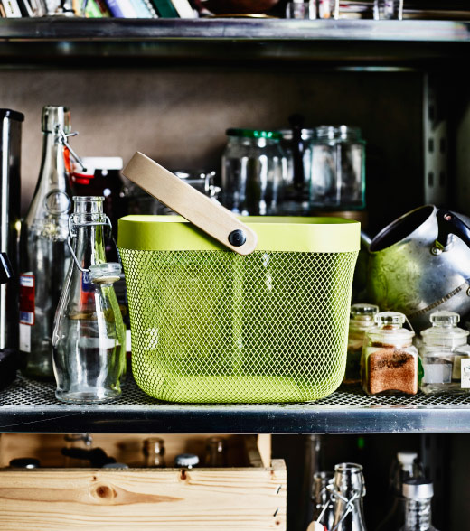 A green mesh basket with handle standing on a shelf.