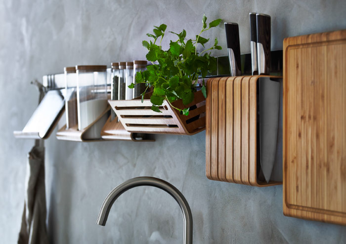 A display of tablet stand, holder with containers, basket, knife holder and a chopping board, all made of bamboo and hanging on a rail.