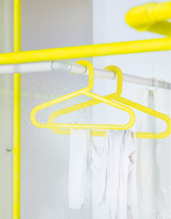 Two yellow clothes-hangers hanging on a rod.