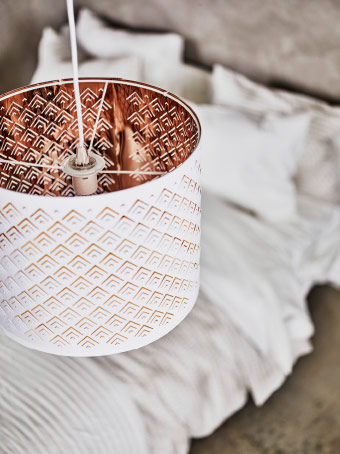 A lamp shade with a perforated pattern. White on the outside and copper-colour on the inside.