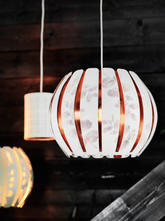 A copper-coloured lamp shade with white stripes.